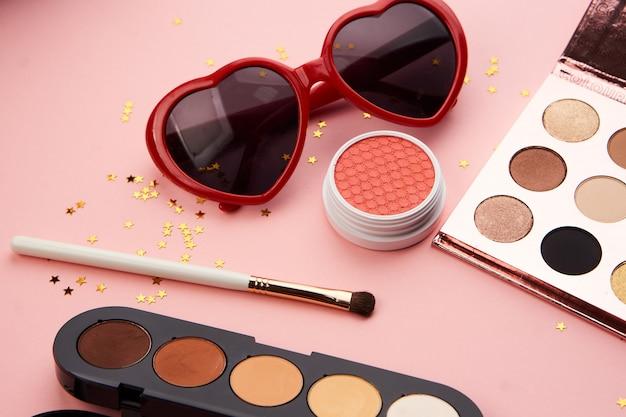 Produits de beauté sur une table rose, maquillage et lunettes de soleil