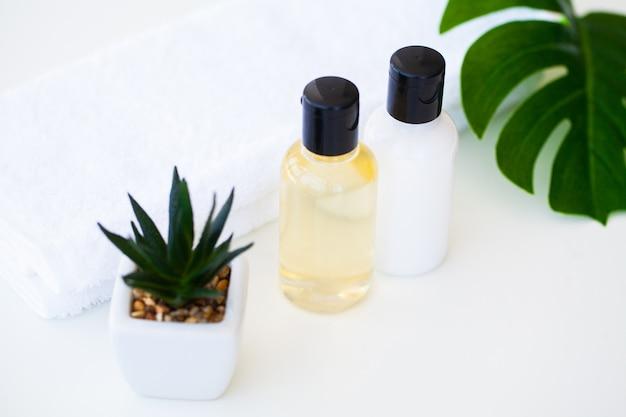 Produits de bien-être et cosmétiques. soins pour les plantes et minéraux. pots de crème, bouteilles cosmétiques blanches. sans étiquette. spa set avec du savon et une serviette blanche.