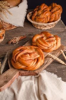 Produits de boulangerie frais délicieux petits pains en osier à la cannelle sur un fond en bois