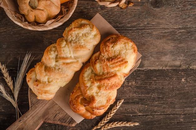 Produits de boulangerie frais - délicieux petits pains en osier avec garniture sur un fond en bois avec copie espace