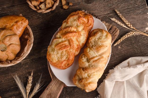 Produits de boulangerie frais - délicieux petits pains en osier avec garniture sur fond de bois