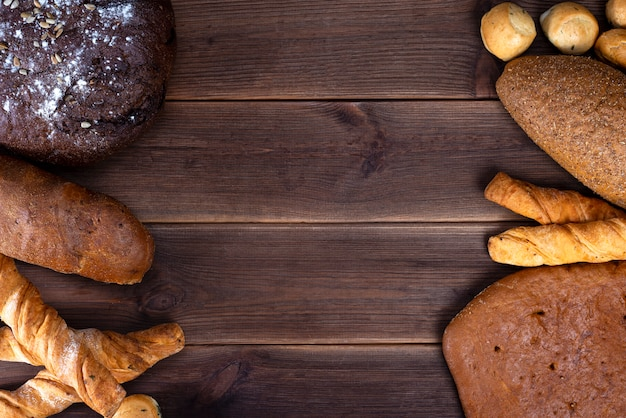 Produits de boulangerie frais, miches de pain croustillant rustique et muffins sur une table en bois.