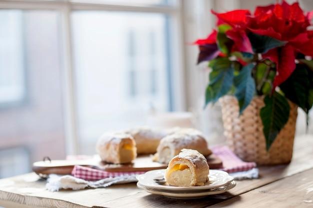 Produits de boulangerie de noël sur une table près d'une fenêtre et une fleur avec des feuilles rouges