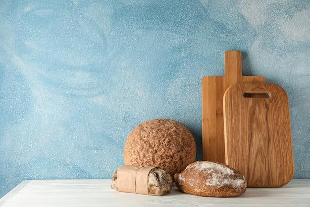 Produits de boulangerie et planches à découper sur une table en bois blanc contre l'espace lumineux, espace pour le texte