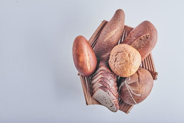 Produits de boulangerie sur table blanche dans un panier en bois.