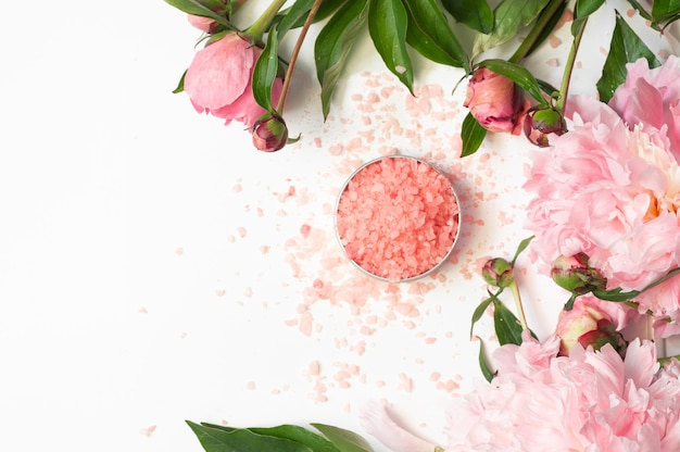 Produits cosmétiques biologiques naturels avec des fleurs de pivoines roses sur fond blanc. spa relax traitements et massage anti-cellulite. beauté, cosmétiques naturels pour spa de bain, soins de la peau, pose à plat.