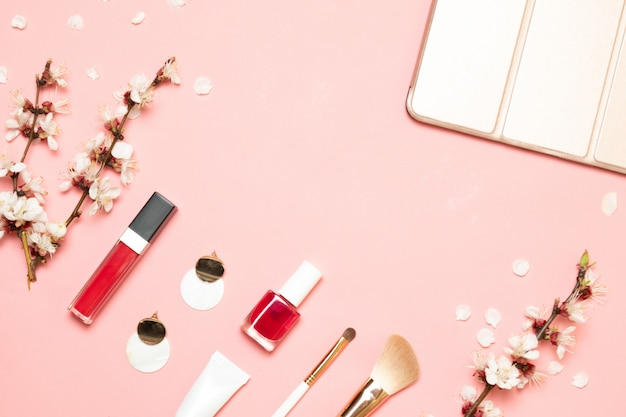 Produits cosmétiques, boucles d'oreilles, sac à main sur fond rose. lay plat, vue de dessus