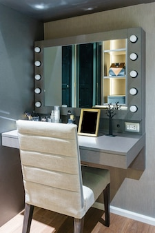 Produits cosmétiques décoratifs et des outils sur la coiffeuse près du miroir dans la salle de maquillage