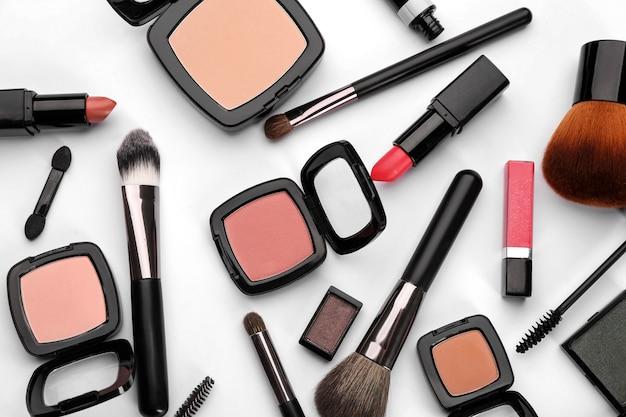 Produits cosmétiques décoratifs et outils de maquilleur professionnel sur tableau blanc
