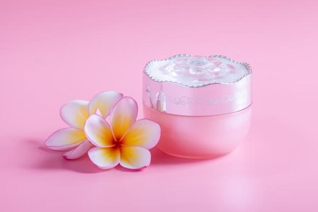 Produits cosmétiques à la fleur de plumeria sur une rose