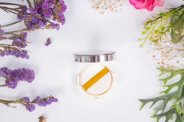 Produits cosmétiques et fleurs sur blanc