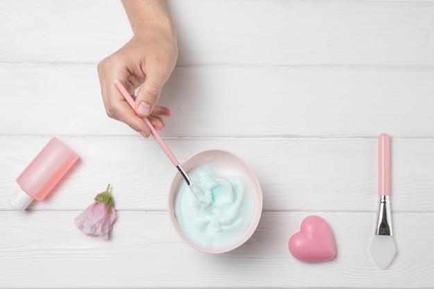 Produits cosmétiques mains plat poser sur fond en bois blanc