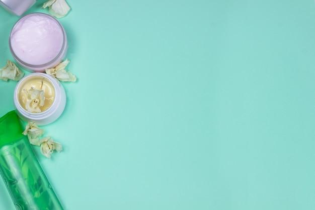 Produits cosmétiques naturels sur fond bleu. pots, bouteilles de crème bio