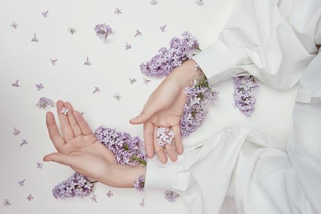 Produits cosmétiques naturels pour les mains en fleurs et pétales de lilas. hydrate et adoucit la peau des mains. des fleurs lilas dépassent des manches du bras