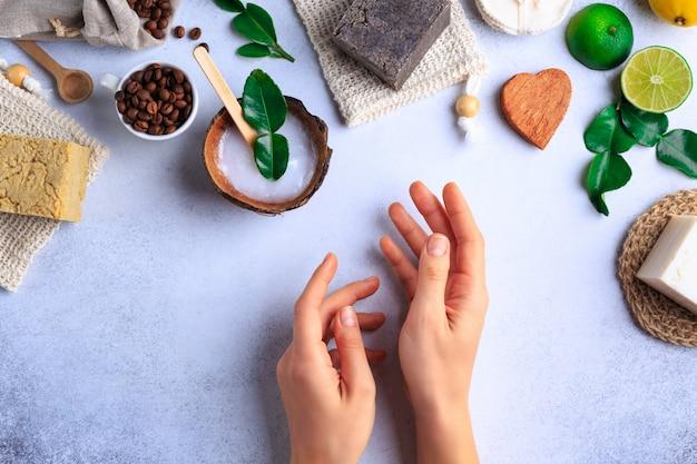Produits cosmétiques naturels avec des savons et des herbes fraîches vue de dessus des mains de femme