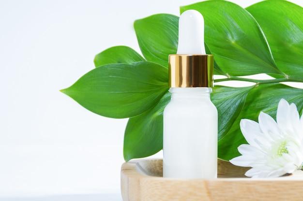 Produits cosmétiques naturels: sérum avec compte-gouttes, fleur blanche et feuilles vertes