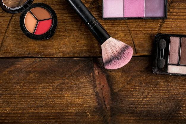 Produits cosmétiques avec pinceau de maquillage sur fond en bois
