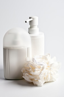 Produits cosmétiques pour le bain et éponge blanche à la lumière