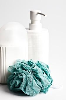 Produits cosmétiques pour le bain et éponge verte à la lumière
