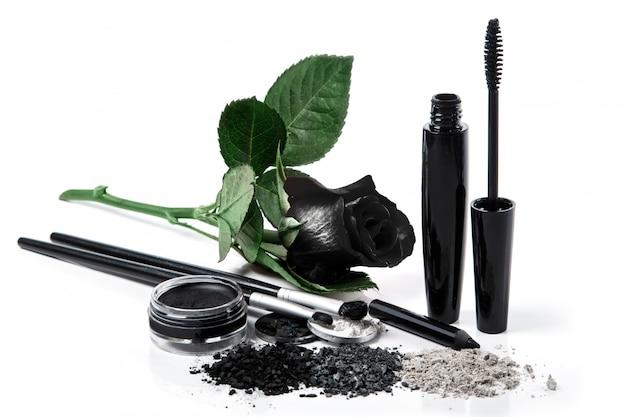 Produits cosmétiques et rose noire sur fond blanc