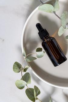 Produits cosmétiques de soins de la peau dans un compte-gouttes en verre foncé avec eucalyptus sur fond clair. mise à plat, espace de copie
