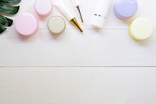 Produits cosmétiques et soins de la peau et des feuilles vertes sur la table en bois blanc