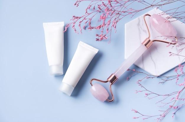 Produits cosmétiques, tubes de crème et rouleau de visage sur une table bleue
