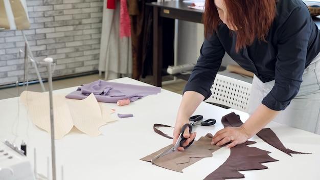 Produits de coupe et de couture dans les entreprises de couture. tailleur femme coupant les détails du tissu travaille dans l'entreprise d'atelier de couture. découpe aux ciseaux en zigzag. couturier créant un nouveau produit.