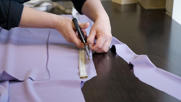 Produits de coupe et de couture dans les entreprises de couture. tailleur femme coupant le tissu à l'aide de grands ciseaux en suivant les marques de craie du motif, gros plan sur les mains. couturier créant de nouveaux vêtements.