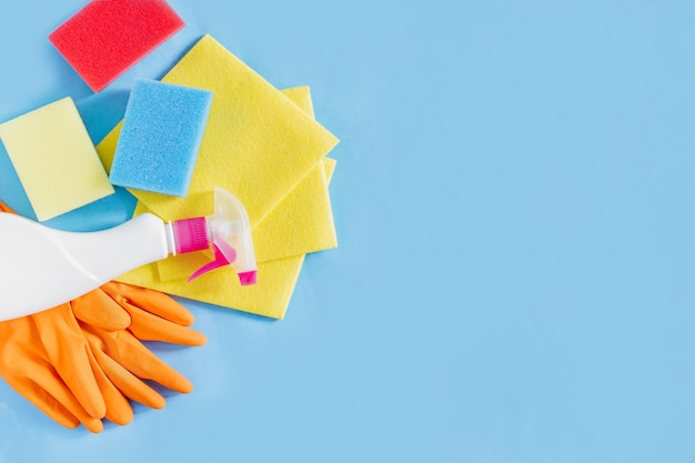 Produits de désinfection et de nettoyage gants en caoutchouc, détergent, éponges et serviettes sur fond bleu