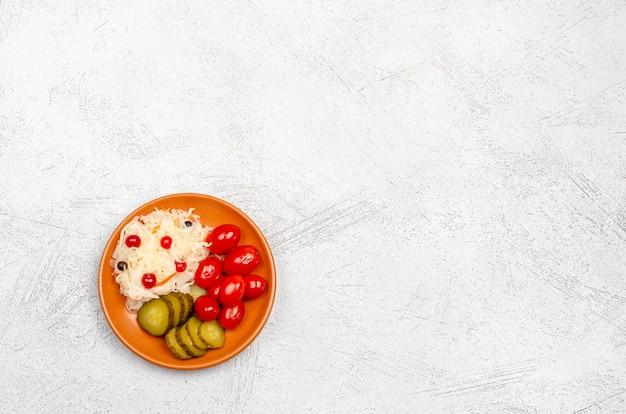 Produits fermentés faits maison sur une assiette, choucroute, tomates marinées, cornichons, fond gris clair.