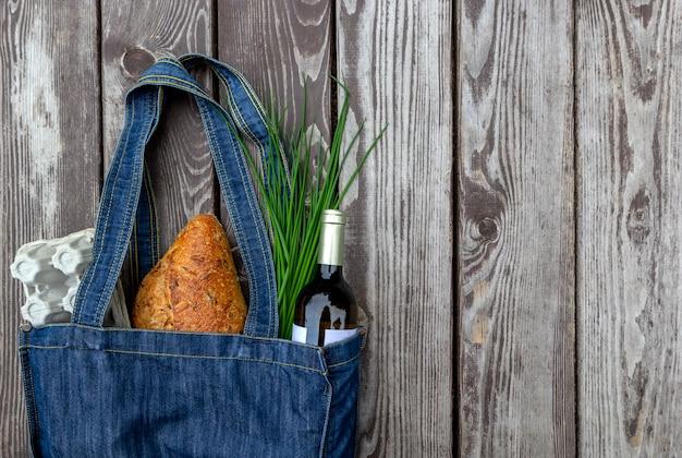 Produits frais au marché (œufs, pain, oignons, bouteille de vin) dans un sac écologique sur une table en bois.