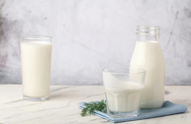 Produits laitiers, concept santé, en verrerie, sur fond gris clair.
