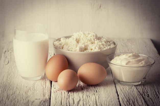 Produits laitiers frais et œufs sur table en bois rustique, photo teintée