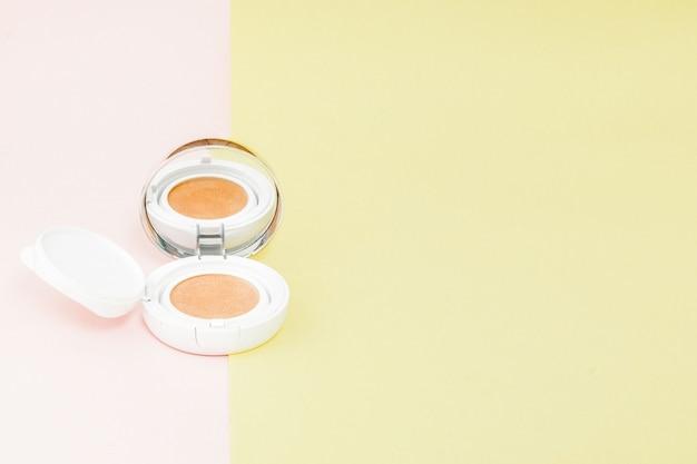 Produits de maquillage débordant sur un fond jaune et rose vif avec espace copie