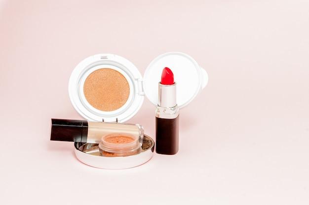 Produits de maquillage débordant sur un fond rose vif avec espace copie