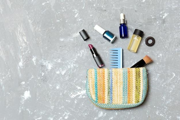 Produits de maquillage déversés hors du sac de cosmétiques sur fond de ciment gris avec un espace vide pour votre conception