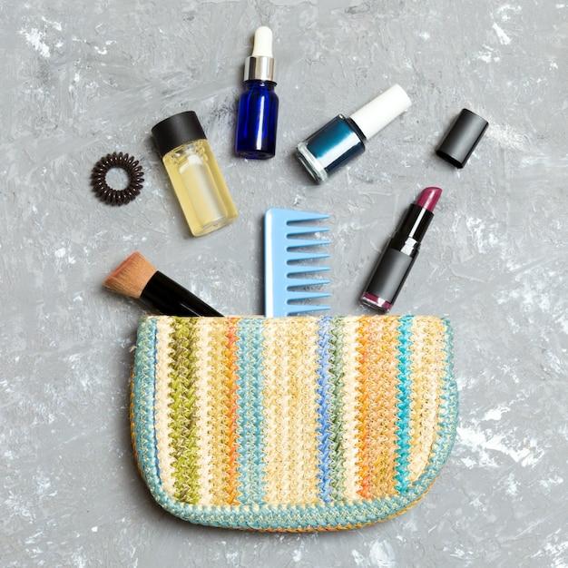 Produits de maquillage déversés hors du sac de cosmétiques, sur fond de ciment gris avec vide