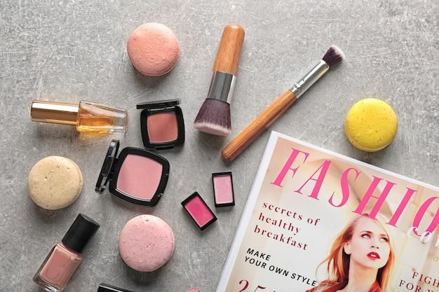 Produits de maquillage, magazine et macarons sur gris texturé