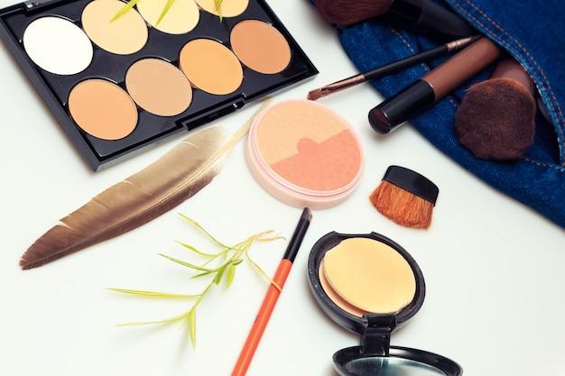 Produits de maquillage et produits de beauté cosmétiques déversés sur un jean en denim pour femme