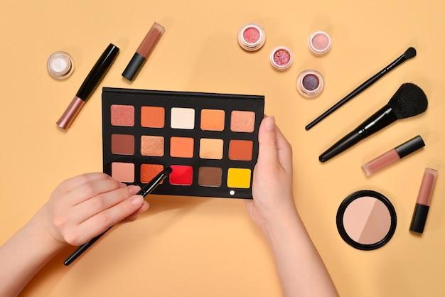 Produits de maquillage professionnels avec fond de teint, rouge à lèvres, ombres à paupières et pinceaux