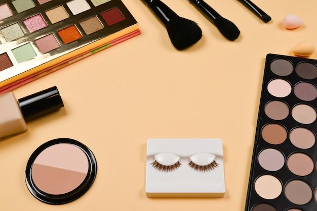 Produits de maquillage professionnels à la mode avec produits de beauté cosmétiques, fond de teint, rouge à lèvres, ombres à paupières, cils, pinceaux et outils.