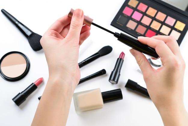 Produits de maquillage professionnels avec produits de beauté cosmétiques, fond de teint, rouge à lèvres, ombres à paupières, cils, pinceaux et outils. mascara dans les mains de la femme.