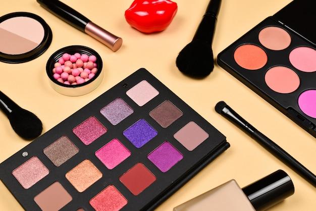 Produits de maquillage professionnels avec produits de beauté cosmétiques, fond de teint, rouge à lèvres, ombres à paupières, cils, pinceaux et outils.
