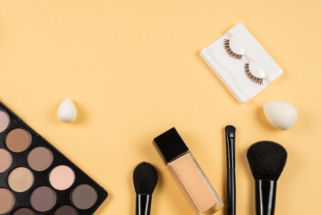 Produits de maquillage professionnels avec produits de beauté cosmétiques, ombres à paupières, cils, mélangeur de beauté, fond de teint, pinceaux et outils.