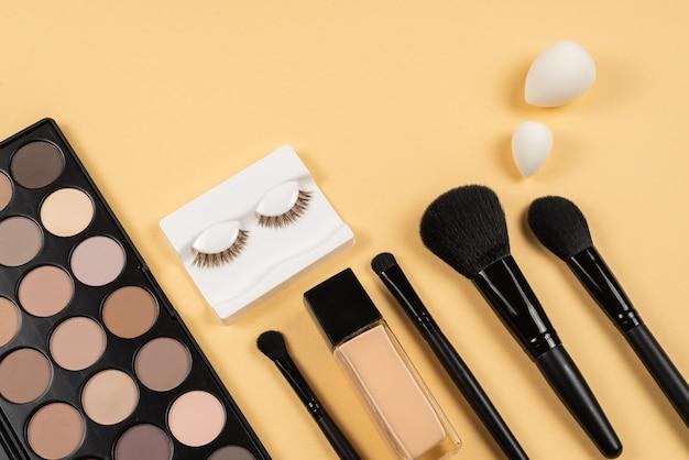 Produits de maquillage professionnels avec des produits de beauté cosmétiques, des ombres à paupières, des cils, un mélangeur de beauté, un fond de teint.