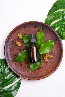 Produits naturels de beauté avec des capsules de gel omega 3 et du sérum dans des bouteilles en verre, des feuilles vertes sur une plaque en bois blanc
