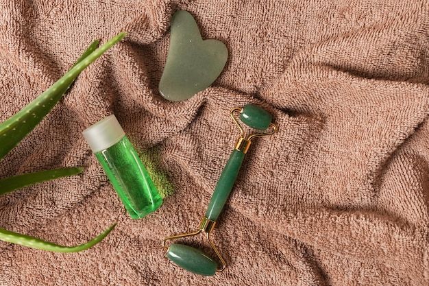 Produits naturels de soins de la peau et de spa rouleau de visage en jade vert et pierre de gua sha à l'aloe vera