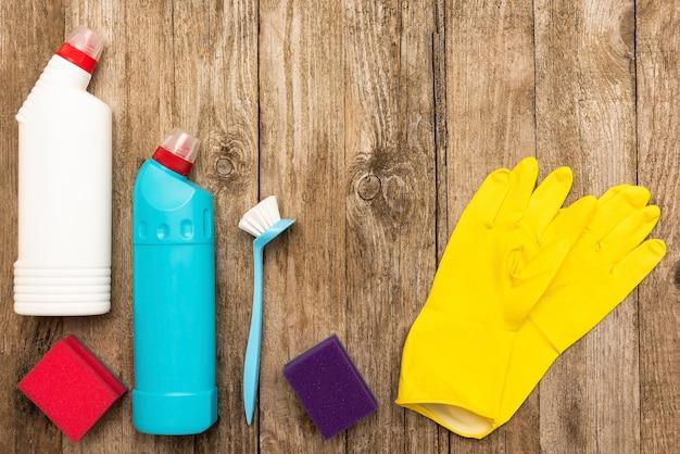 Produits de nettoyage et chiffons sur un fond en bois.