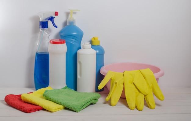 Produits de nettoyage à domicile avec des serviettes colorées sur un espace blanc